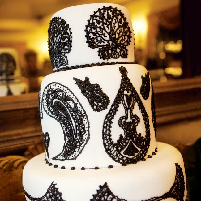 A black-and-white brocade pattern was another major theme element for Amber and Chad. In addition to being piped onto their elegant wedding cake and incorporated into their invitations, wallpaper in that pattern was used for the aisle runner and as a backdrop for a photo guest book.
