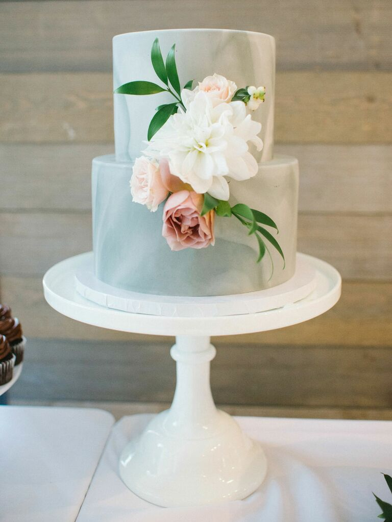 Two-tier blue wedding cake with fresh flowers at summer wedding