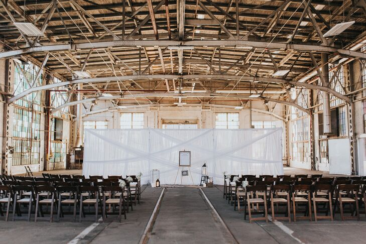 Teresa and Chris used a white-draped backdrop to separate their ceremony space from the rest of Rail Yards Market in Albuquerque, New Mexico.
