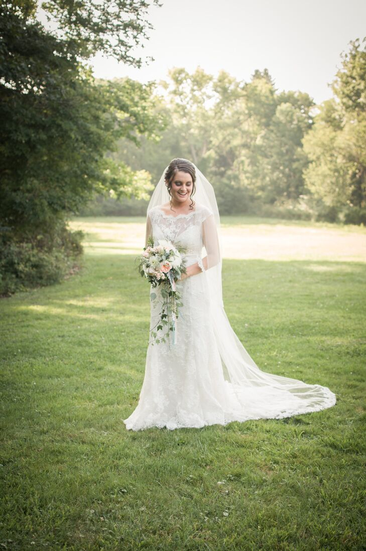 Samantha designed her wedding dress and, with help from Laura from A Bride's Design in Avon, Ohio, created a lace dress with a high neckline and and open back. She paired the dress with a chapel veil with lace edging matching the dress.
