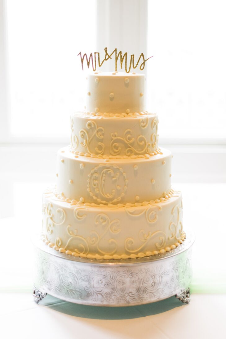 """Pen and Pastry created a four-tier cake with swirly details and Ginnie and Tyler's custom monogram. A """"Mr. & Mrs."""" cake topper completed the classic confection atop a metallic cake stand."""