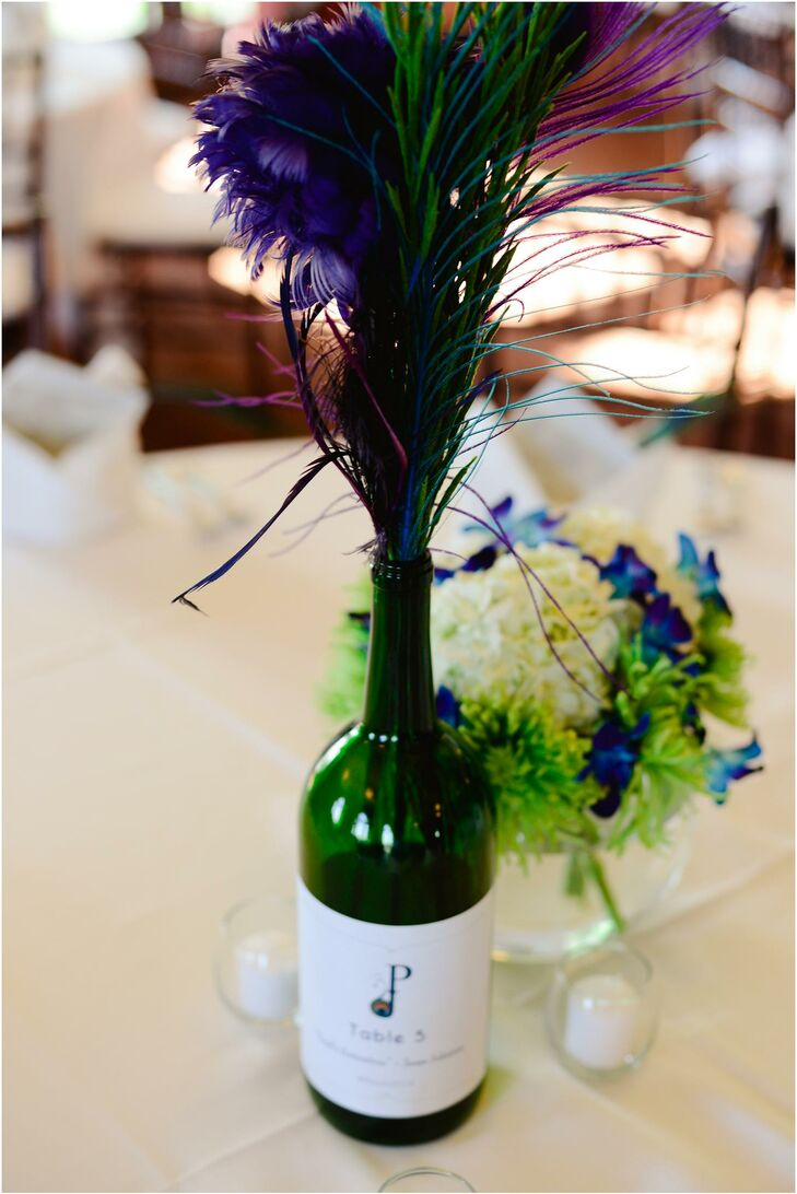 The table decor had wine bottles with custom labels made by the bride. The bride and groom cut the bottoms off the wine bottles to repurpose them as DIY candleholders and peacock feather vases.