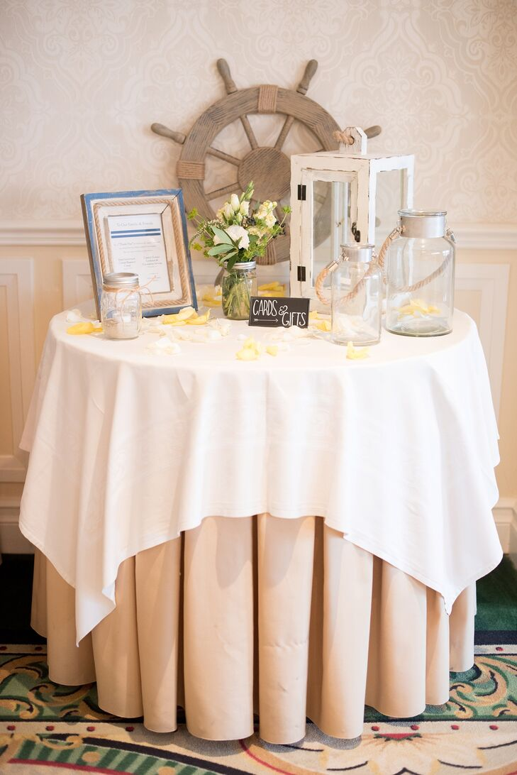 Their card and gift display hinted at the nautical theme with a few understated accents. A shabby-chic white lantern and duo of glass lanterns surrounded its chalkboard sign along the table. A wooden ship wheel also marked the back. If that wasn't enough, rope coiled around the couple's other framed sign.