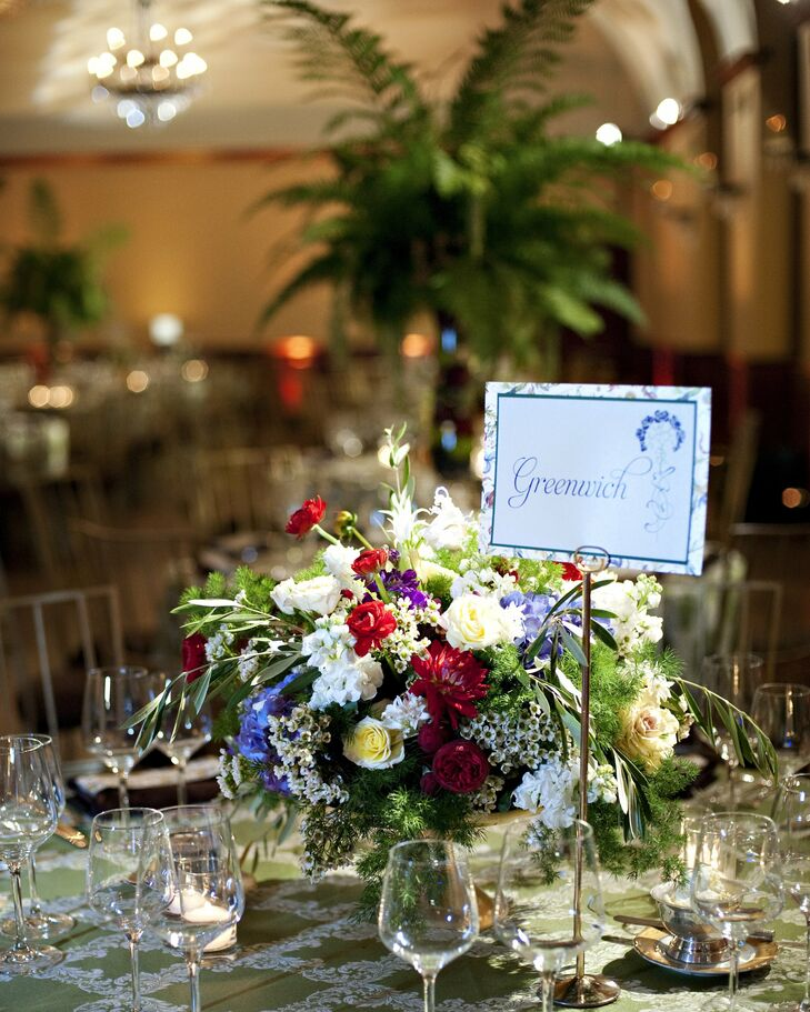 Some of the reception tables were decorated with gold cake plates topped with amaranthus, blue and purple hydrangeas, yellow spray roses, red dahlias and pink coxcomb.