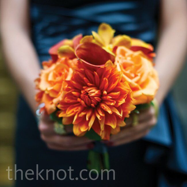 Brightorange dahlias, calla lilies, roses and orchids really popped against the gray-blue bridesmaid dresses.