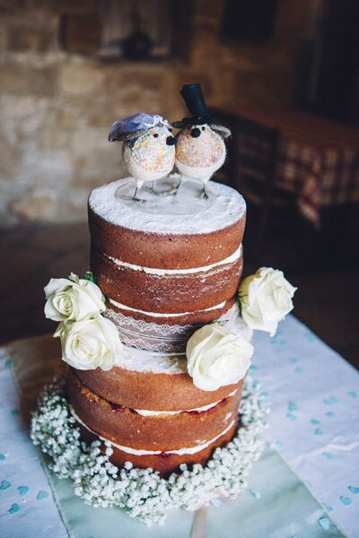 """The couple chose a naked cake from Marianna's Bakery in Cyprus which perfectly fit in with the natural, rustic surroundings of the inn. """"We decided upon a Vanilla sponge with jam and buttercream for the bottom layer with a chocolatey top tier,"""" says Rachel. Rachel found two love birds to sit on top from Liberty Rose vintage store in Buckinghamshire, UK."""