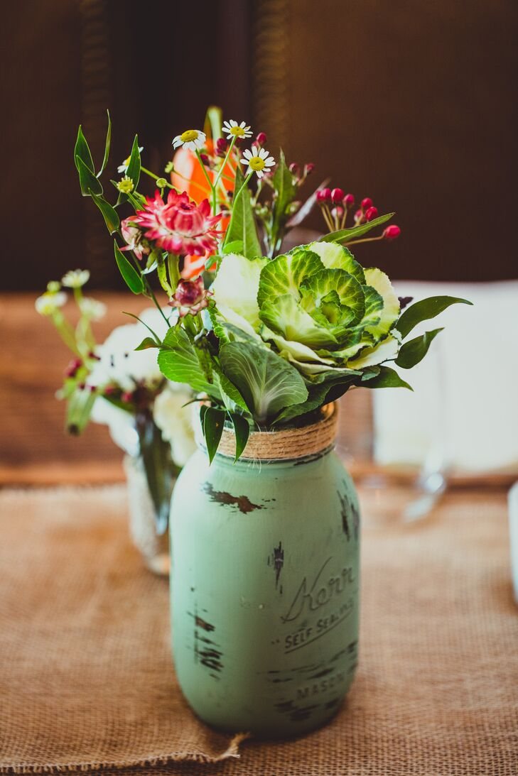 Green and pink arrangements filled green painted mason jars and served as table centerpieces.