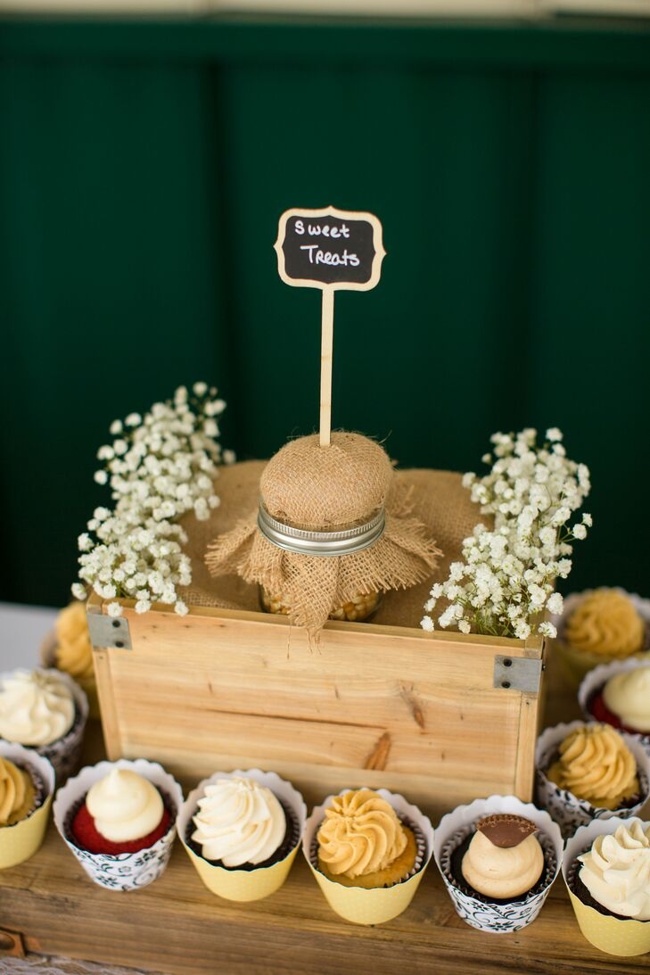 "A variety of flavored cupcakes displayed on wooden boxes embodied the rustic vibe of the wedding at Herot Hall Farm in Kenna, West Virginia. The top of the display had a chalkboard sign that read ""sweet treats"" accented with baby's breath on the sides."