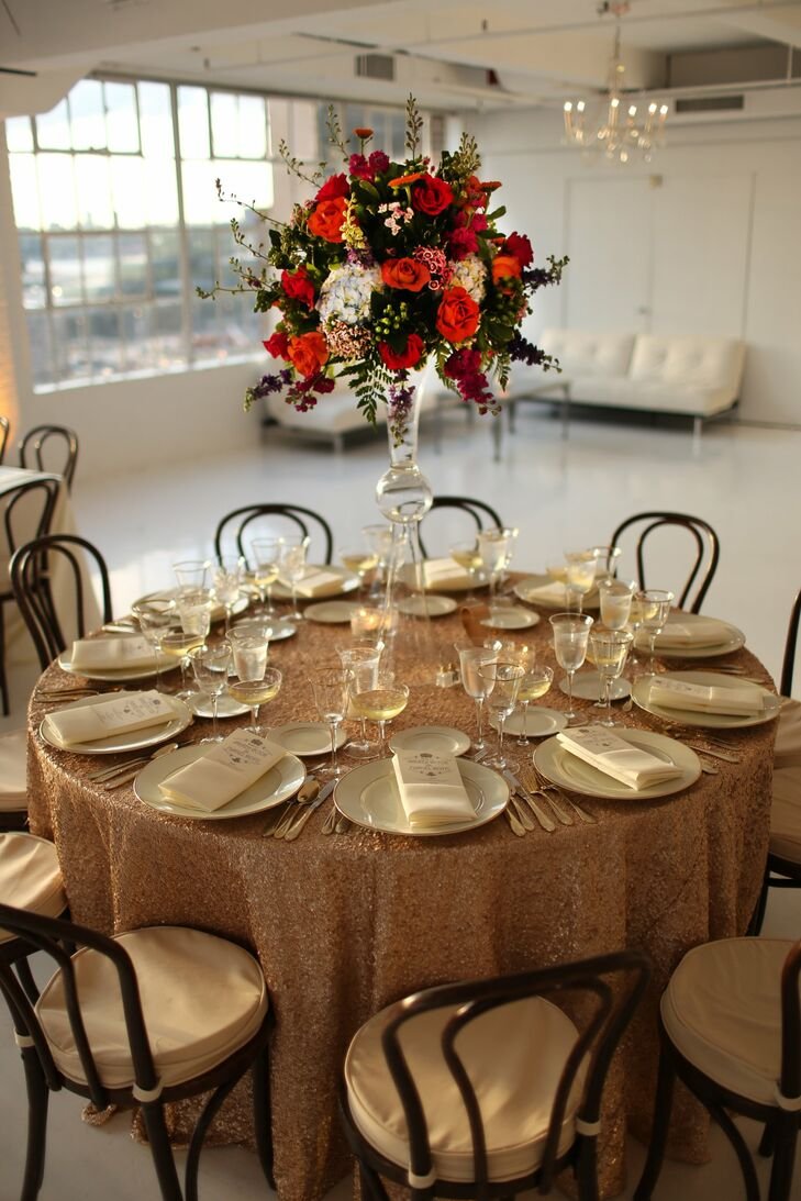 Andrea and Manuel chose a combination of round and square tables for the reception as well as high and low centerpieces made up of bright, jewel-toned flower arrangements. The tablecloths were a mixture of a basic beige and a gold sequin.