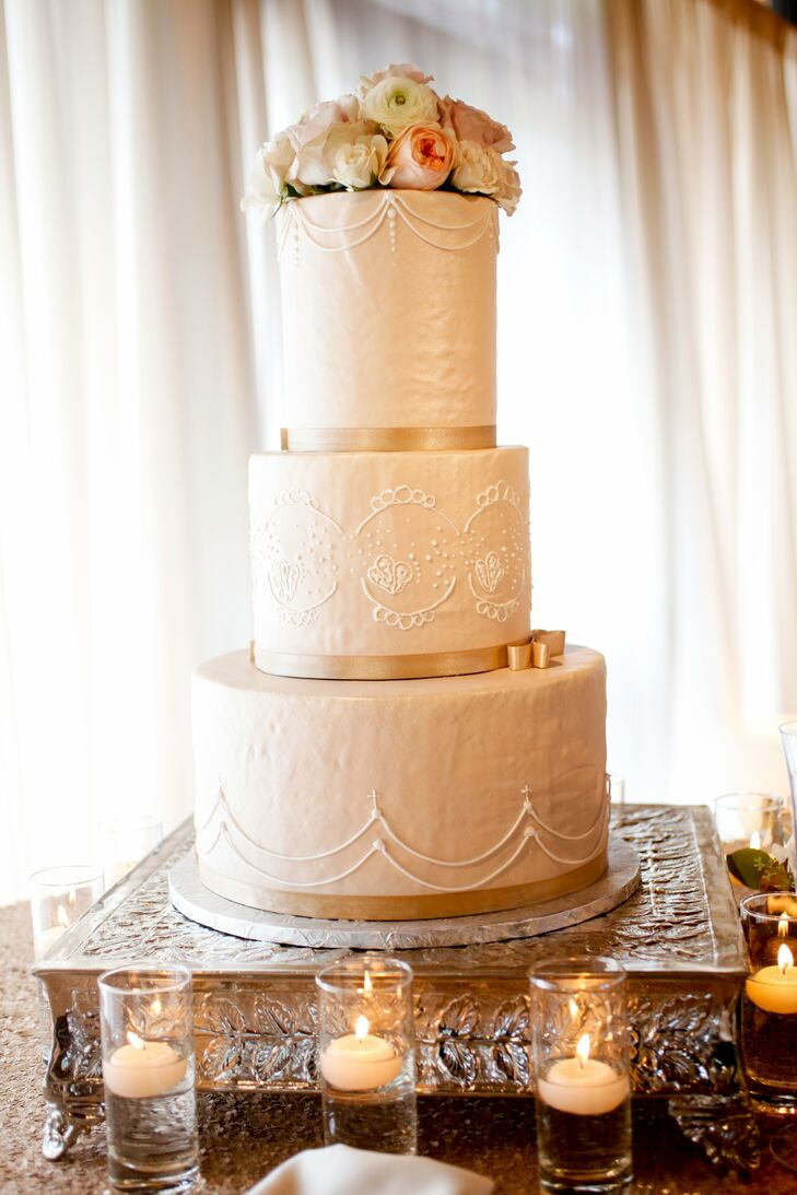 The couple's traditional wedding cake had romantic piping and was topped with fresh flowers in blush and peach.
