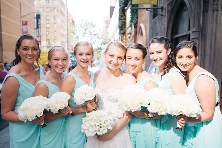 The bride's attendants wore short Jim Hjelm dresses in Tiffany blue. The bridesmaids wore black sashes, and the Maids of Honor wore white sashes. All carried simple bouquets of white roses.