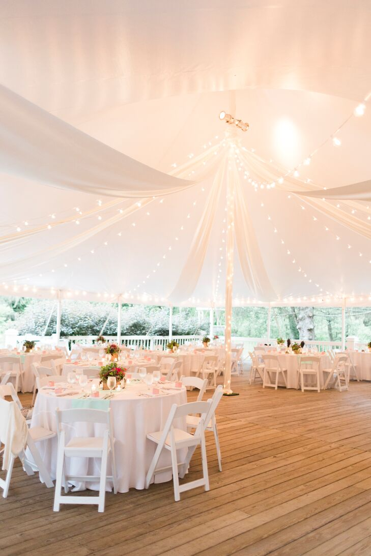 The reception took place on a wooden patio under an open-air tent. The space was illuminated with string lights that hung from the canopy of the tent. Round dining tables were set up with white folding chairs for the event.