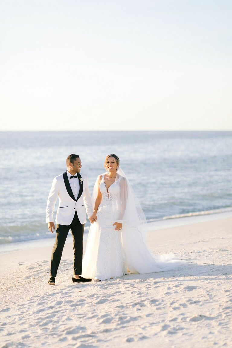Couple in black-tie attire holding hands on the beach