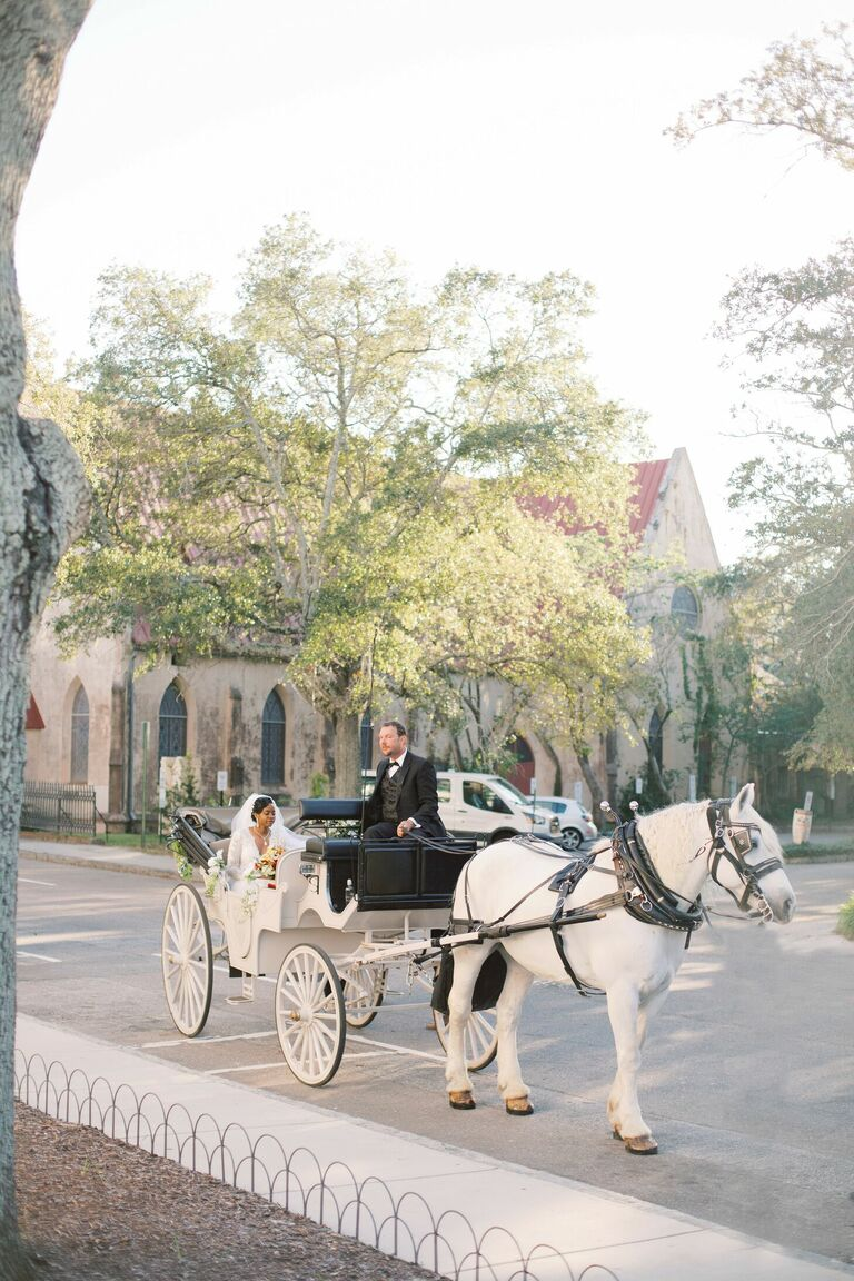Bride arriving to ceremony in horse-drawn carriage