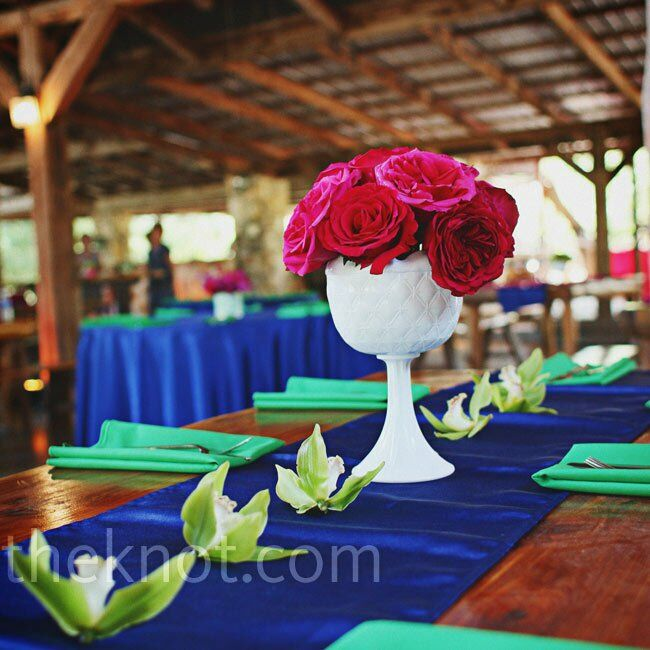 Vibrant linens (sapphire runners and emerald napkins) popped against the bare-wood tables. Stemmed milk-glass vases filled with hot-pink flowers added even more color.