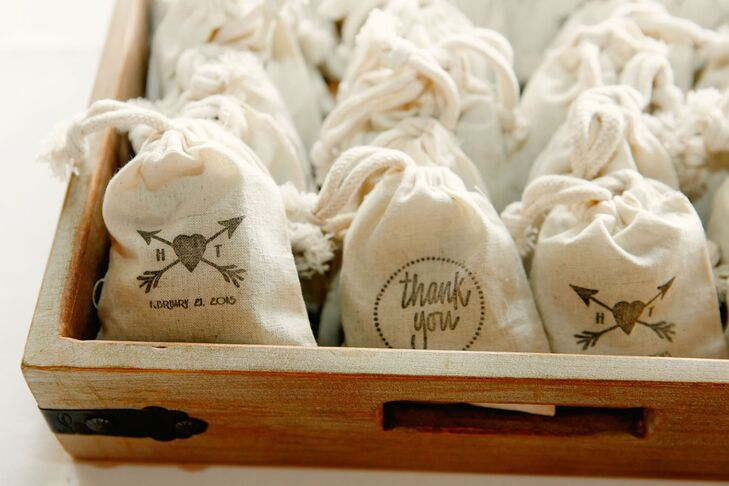 "For wedding favors, the bride hand-stamped muslin sachets. One side said ""thank you,"" and the other was the crossed-arrow wedding logo. The bride filled the sachets with dried lavender, so guests could toss some as Hailey and Tyler made their grand exit and keep some to remember the day."