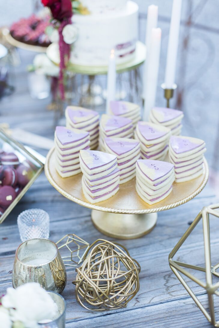 For an addition to the dessert spread, Paper Cake Events designed violet sugar cookies frosted with the couple's initials. Warm gold and brass votive candles added warmth to this table.