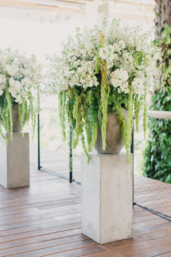 """""""It was so lush and perfect,"""" Kristin says. Their twin arrangements from the Flower Bazaar marked the ceremony space with an abundance of greenery. Hanging amaranthus, white delphiniums and baby's breath all filled each stone urn on matching stone pedestals. The design couldn't have looked more natural!"""