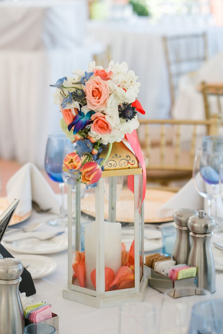 Their centerpieces brought out the couple's wedding colors with a chic design. Coral rose petals and white candles filled silver and gold lanterns for a fun contrast. Florists from Atmospheres Floral and Decor topped each one with a lush display of blue sea holly, coral tulips, peach roses, white hydrangeas and peach hypericum berries.