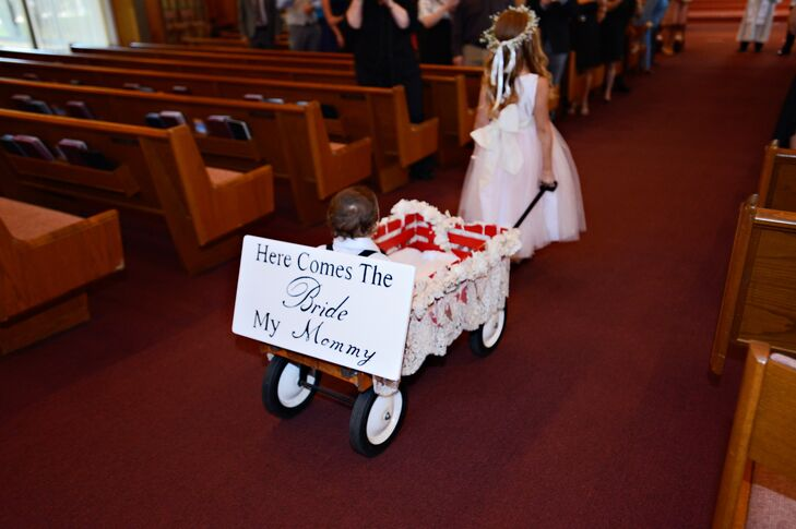 """The couple's son was pulled in a wagon down the aisle with a sign on the back that read, """"Here Comes the Bride: My Mommy."""""""