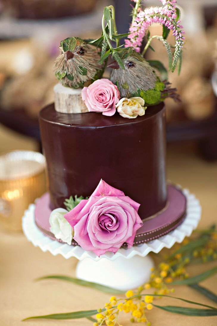 Jami and Eric cut into a small chocolate cake that was topped with two tiny birds and fresh flowers.