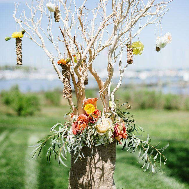 Rustic arrangements of manzanita branches, flowers and greenery were wrapped in burlap at the altar. Single blooms hung from the branches, adding even more texture.