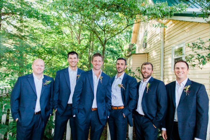 "The groom and his party all wore matching custom navy suits and white shirts open at the neck—with no tie. ""Since this is one of my favorite looks on my husband, I knew that was how I wanted to see him while we were saying our vows!"" says Cory."