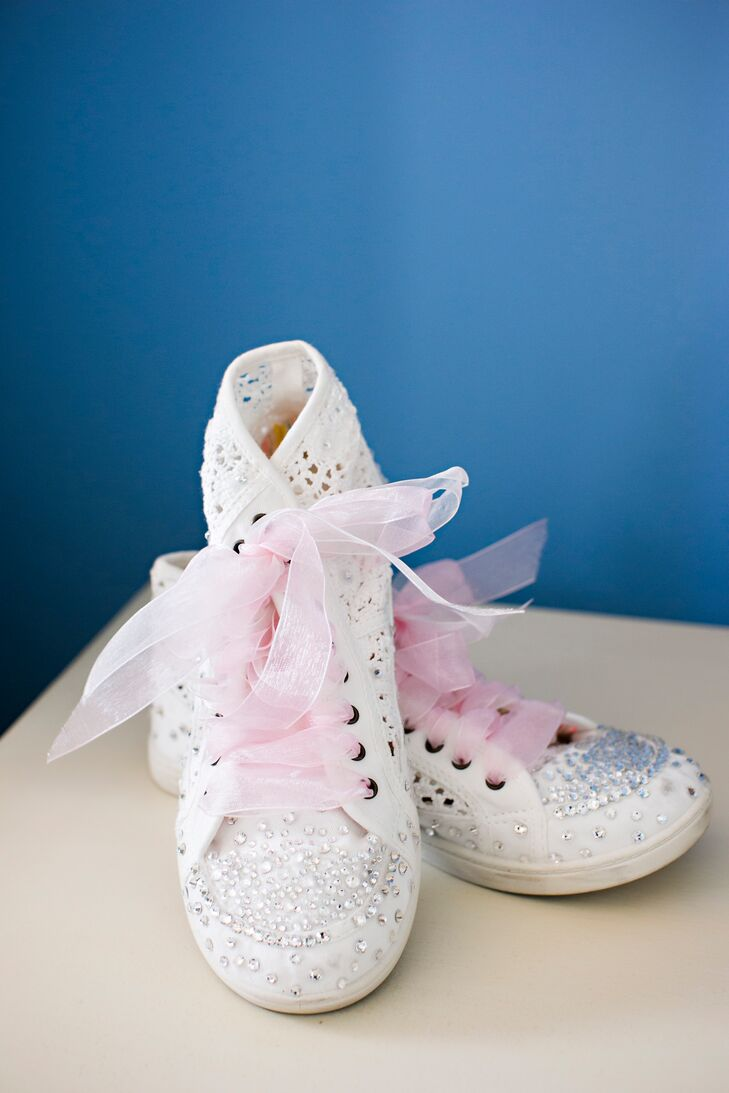 During the reception, Kelley switched her hot pink peep-toe wedding shoes for something a bit more casual, nontraditional and fun: high-top sneakers. Each Swarovski crystal on the shoes mirrored the details on her ivory wedding dress. The pink tulle laces also complemented the couple's pink and white wedding colors.