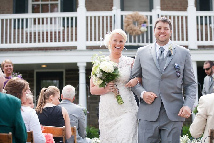Sara wore a form-fitting lace gown on her wedding day. She carried a bouquet with white hydrangeas. Josh wore a gray three-piece suit and a gray tie.