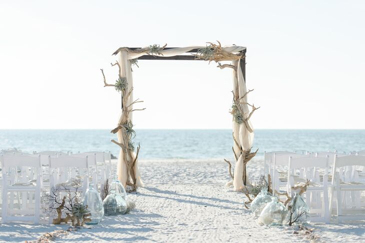 Nicole and Bren allowed the natural scenery take center stage for the ceremony, selecting simple decor that played up the casual, beachy feel at Marco Beach Ocean Resort in Marco Island, Florida. The soft sand aisle was lined with seashells, sea fans, driftwood, air plants and pale blue vases, leading to a striking driftwood arch adorned with air plants and ethereal white fabric.