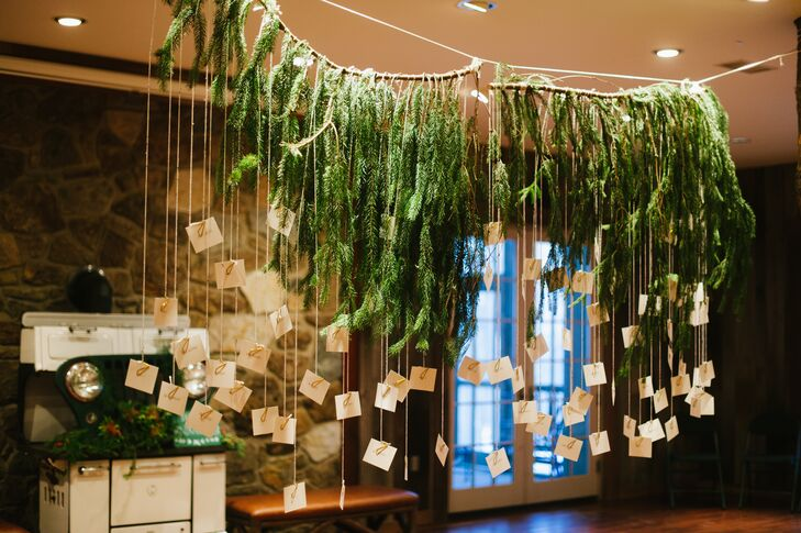 """Our wedding stylist, Rebecca Gallop, hand-wrote and cut all the escort cards,"" Paula says. ""The display was a favorite. We foraged a large, cascading evergreen with cream-colored yarn dangling from it, and attached each escort card by a brass-colored butterfly clip."""