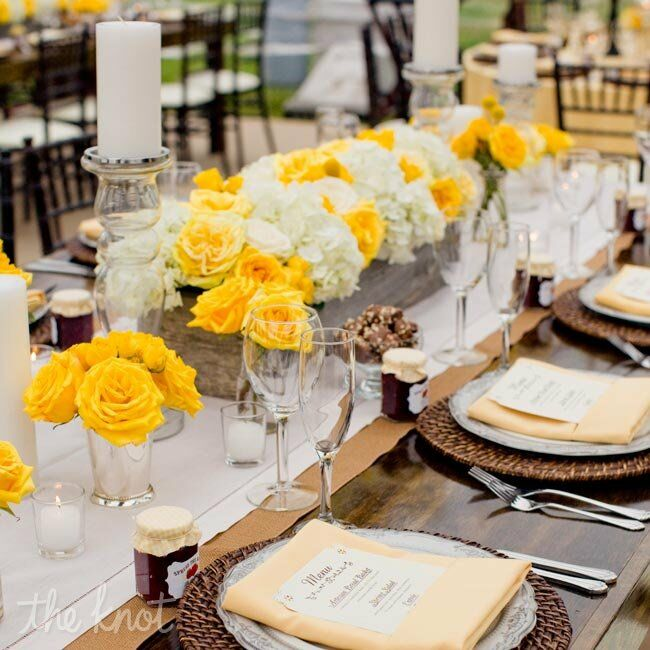 Rustic wooden planters filled with yellow and ivory roses and white hydrangeas added a vibrant touch of spring.