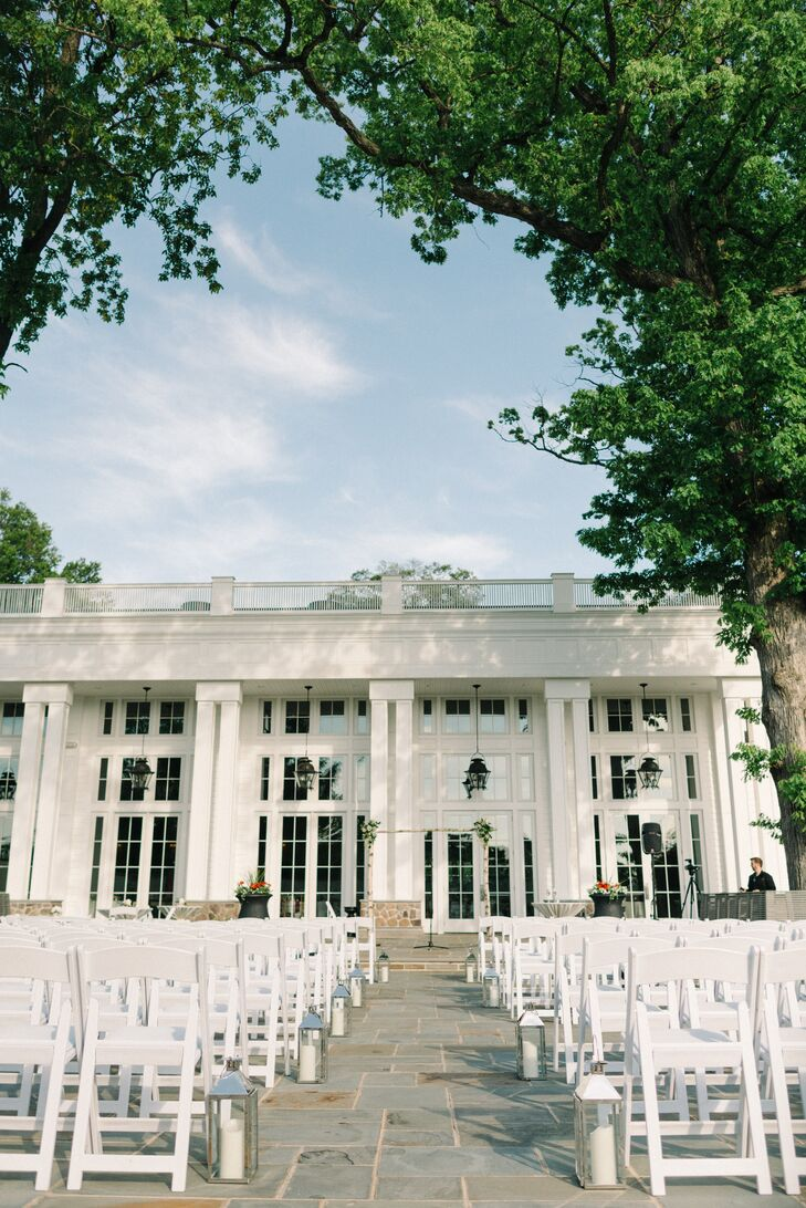 """""""When Steve and I saw the Ryland Inn, the ballroom wasn't even built yet,"""" Sarah says. """"From the minute we walked into the restaurant and took a tour of the grounds, we knew that we'd found the perfect space to host our wedding."""" Their all-white ceremony decor only accented the venue's classic columns and grand windows. The couple paired rows of white folding chairs with modern silver lanterns and a festive birchwood wedding arch."""