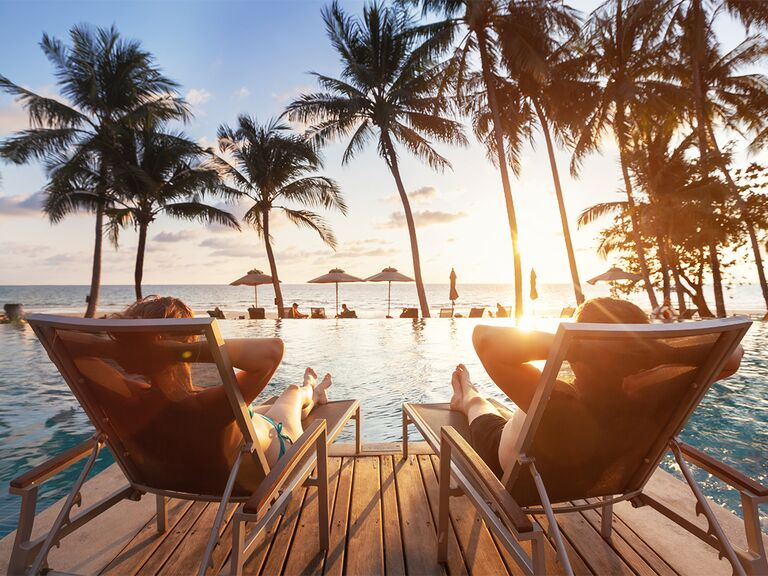 couple lounging on chairs poolside looking at palm trees