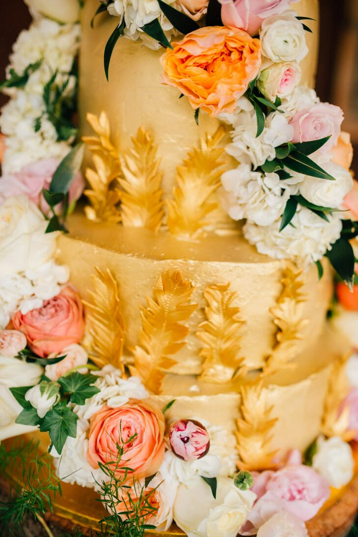 The stunning wedding cake was painted in striking metallic gold with a feather motif and covered with a twisting cascade of fresh flowers.