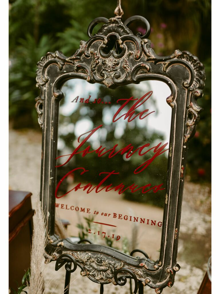 Red calligraphy wedding signage on vintage baroque mirror