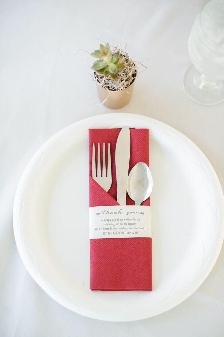 "Paired with ivory linens, the simple place settings featured red disposable napkins wrapped in a thank-you note. ""It was important to us to let our family and friends know how appreciative we were for all their support and for celebrating with us,"" Kelby says."