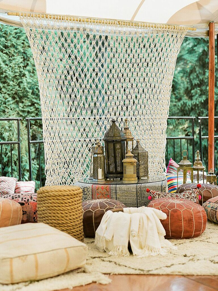 Moroccan-themed seating area inside tented wedding with couches, blankets and poufs