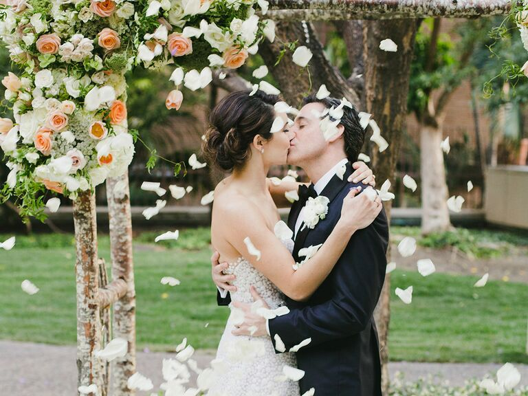 Bride and groom kissing under floral and wood wedding arch