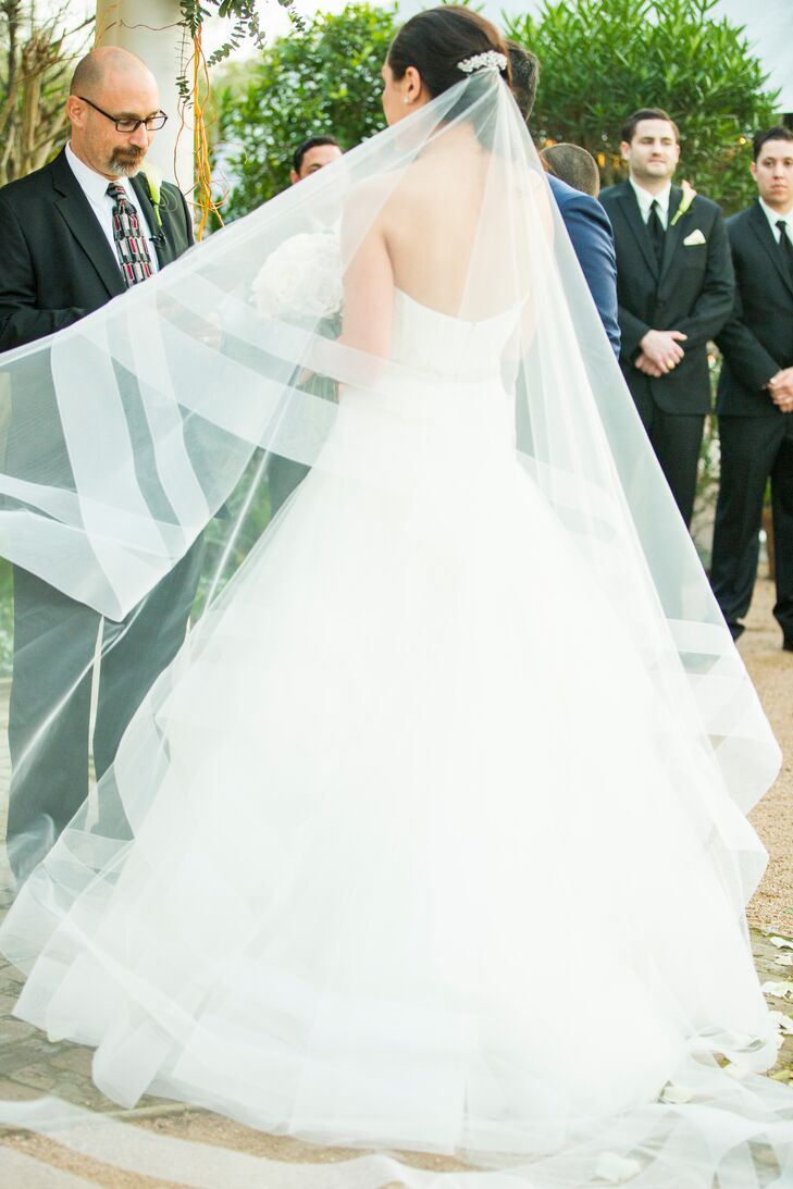 The sheer lines in this cathedral-length veil, which perfectly matched Alexandra's stunning Rivni ball gown wedding dress, added a modern touch to her bridal style.