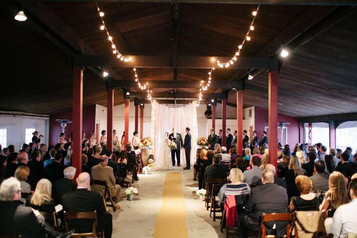 The aisle was lined from above by string lights, adding height and dimension to the pavilion in which Lauren and Stephen were married.