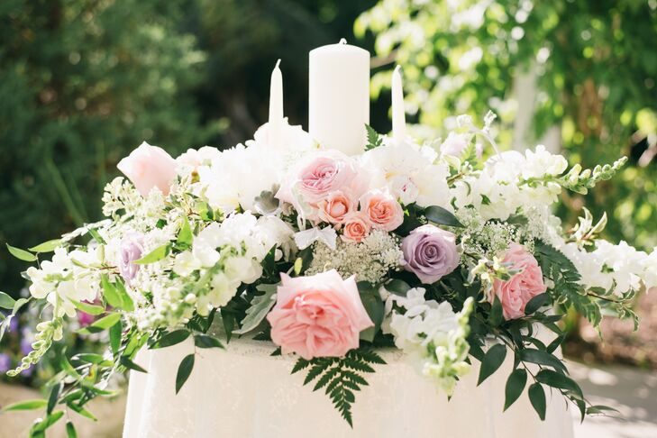 Nicole's mother, a local florist, grew many of the blooms used throughout the big day. The couple's unity table was especially lavish with garden roses and ferns.