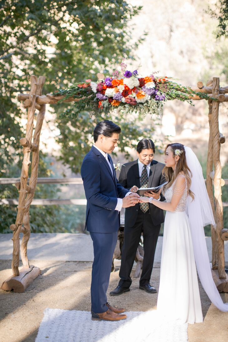 Lisa and Scott exchanged vows in an outdoor creekside ceremony under a wooden arch adorned with a colorful flower arrangement that Lisa had crafted herself.