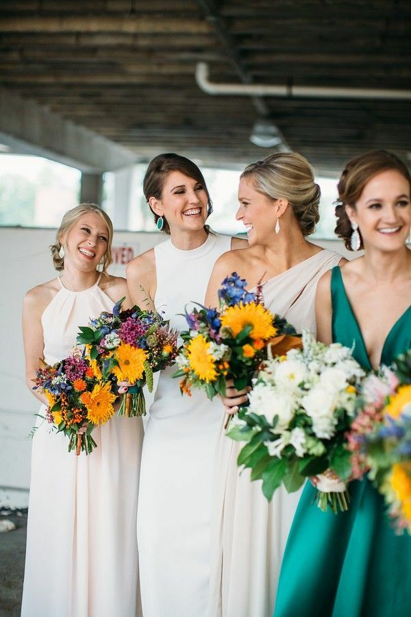 Bridesmaids holding colorful sunflower bouquets