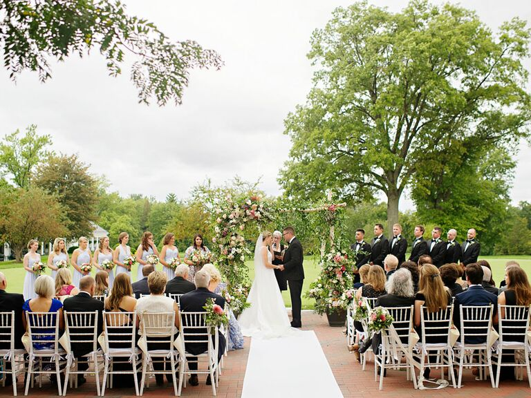 Classic wedding style ceremony outdoors with colorful floral arch