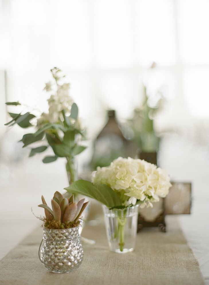Single white, ivory and green blooms were placed in small vases on a burlap runner.