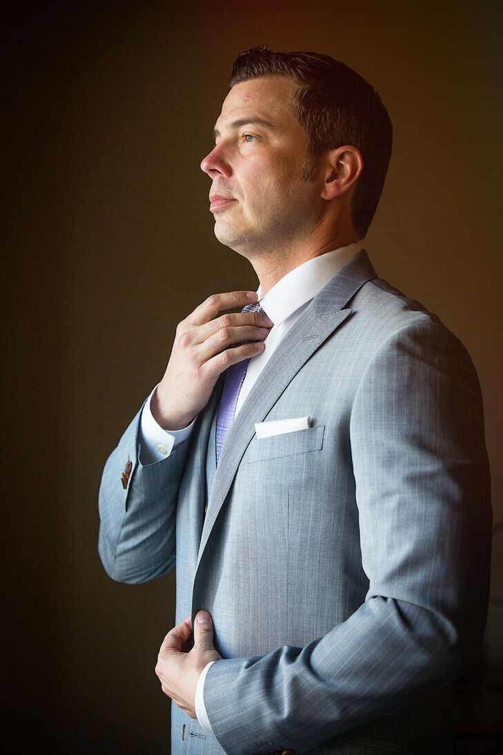Jay dressed in a gray suit on his wedding day. He paired his suit with a lavender tie to match the color palette.