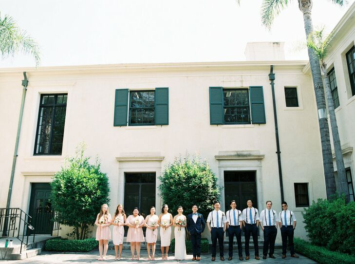 Alison's bridesmaids donned blush-hued knee-length dresses for the relaxed garden wedding. Daniel's groomsmen sported black slacks, collared shirts and suspenders.