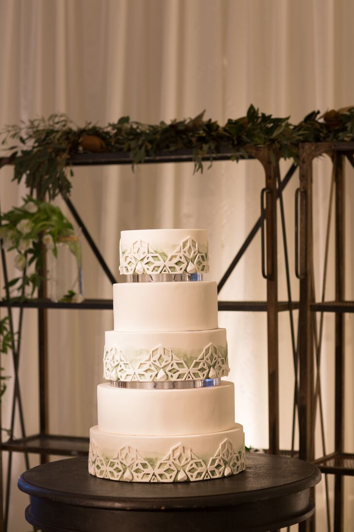 The five-tier wedding cake tied in the white and green colors with a modern design.