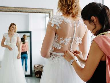 Bride getting help with wedding dress buttons